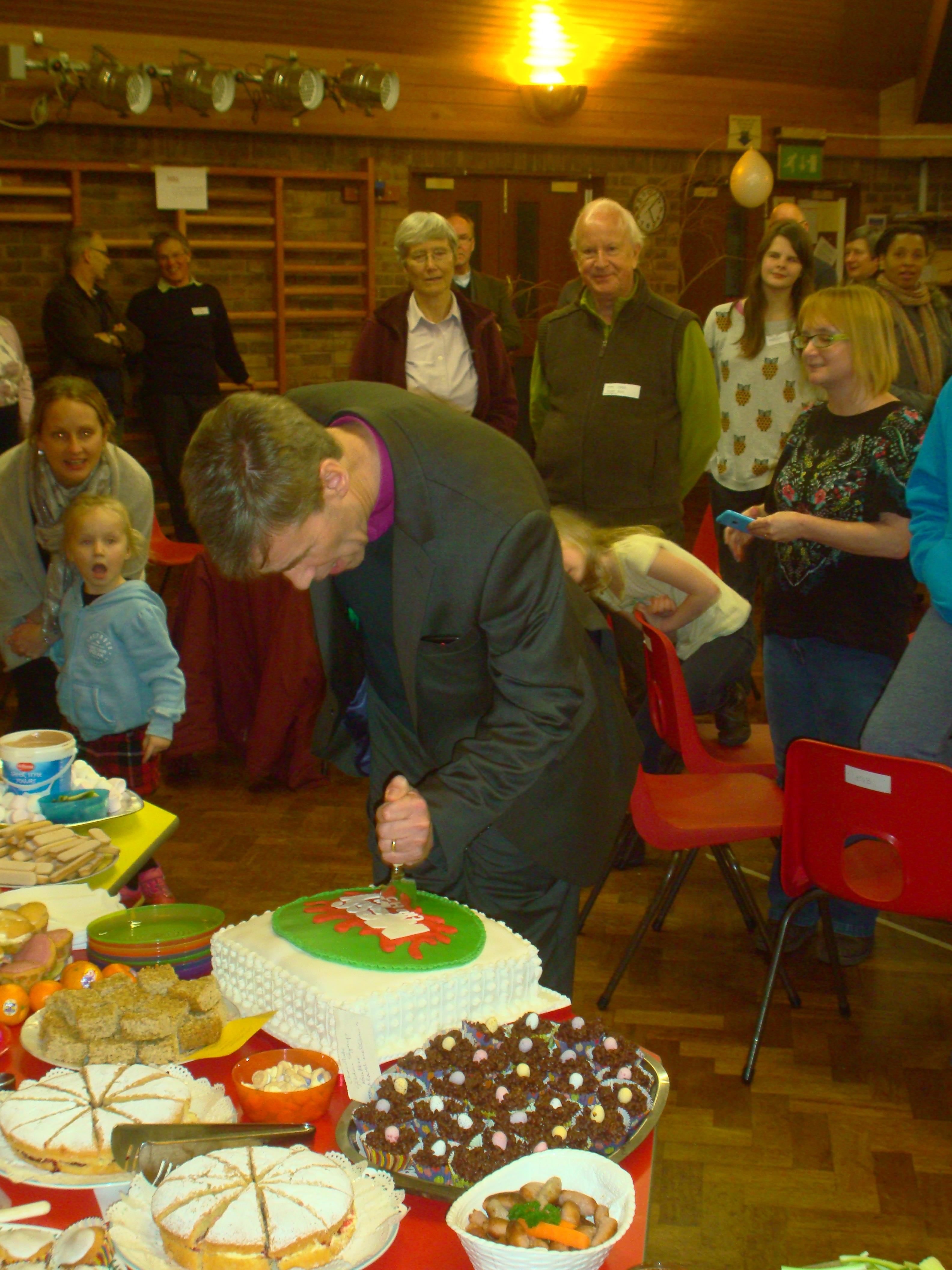 bishop cutting cake